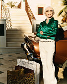 Well-Dressed Wealthy Senior Woman Stands on the Driveway by Her Car With Shopping Bags