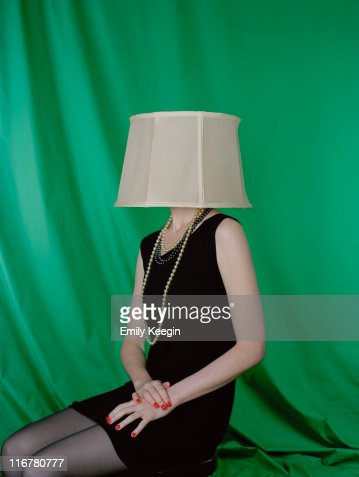 A well-dressed woman wearing a lamp shade on her head