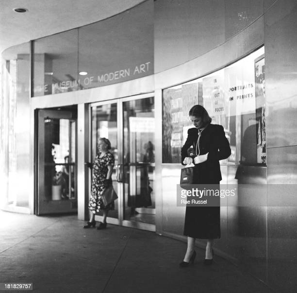 A welldressed woman with a long string of pearls around her neck stands at the entrance to the Museum of Modern Art New York New York 1948