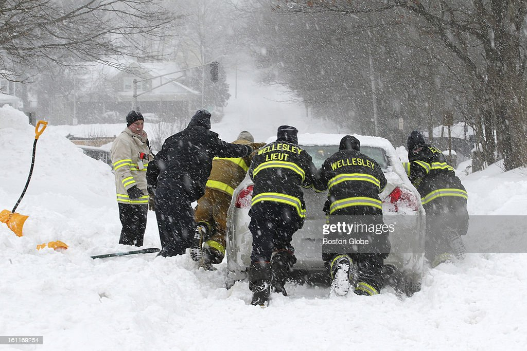 Wellesley firefighters push out fellow firefighter Brian Beckwith after he got stuck in the blizzard approaching the station.