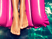 Tanned, well-groomed feet lay in the pool on magenta inflatable mattress for swimming . Pedicure, foot care and Spa.