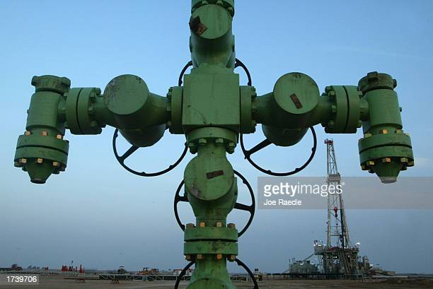 A wellhead is shown in front of a Kuwait Oil Company drilling rig January 22 2003 on the northern border between Iraq and Kuwait in Kuwait Kuwait...
