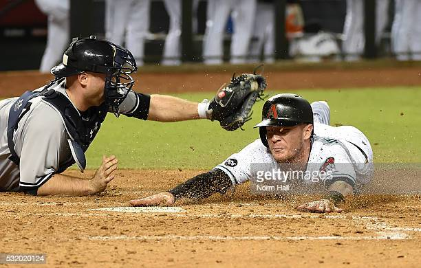 Wellington Castillo of the Arizona Diamondbacks drives in teammate Chris Herrmann who slides into home just ahead of the tag by Brian McCann of the...