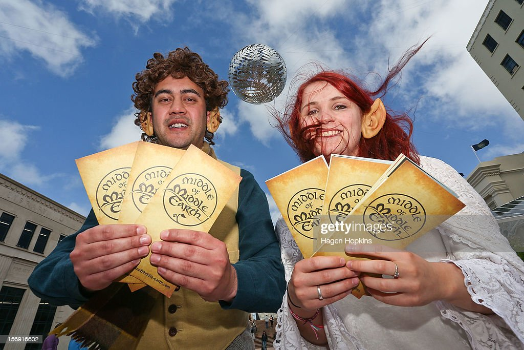 Wellington i-SITE Visitor Information Centre staff Nick Jones and Lauren Campbell pose with 'Middle Earth' brochures ahead of the 'The Hobbit: An Unexpected Journey' world premiere at Civic Square on November 25, 2012 in Wellington, New Zealand.