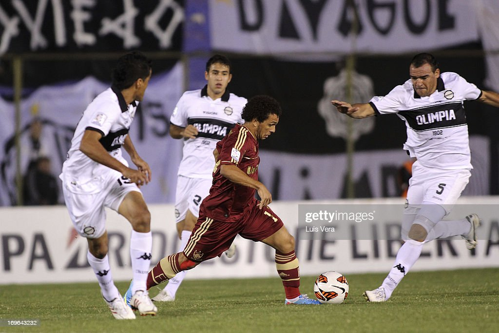 Wellington Nem of Fluminense fights for the ball with Julio Manzur and Salustiano Candia of Olimpia during a match between Olimpia and Fluminense as...