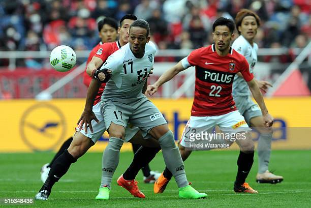 Wellington of Avispa Fukuoka controls the ball under pressure of Tomoaki Makino of Urawa Red Diamonds during the JLeague match between Urawa Red...