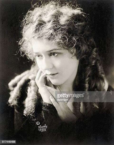 Wellknown American silent film star Mary Pickford Pickford is shown in a headandshoulders portrait with her hands placed delicately near her face...
