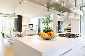Well-lighted space of open plan kitchen area with kitchen island and with the view of dining room