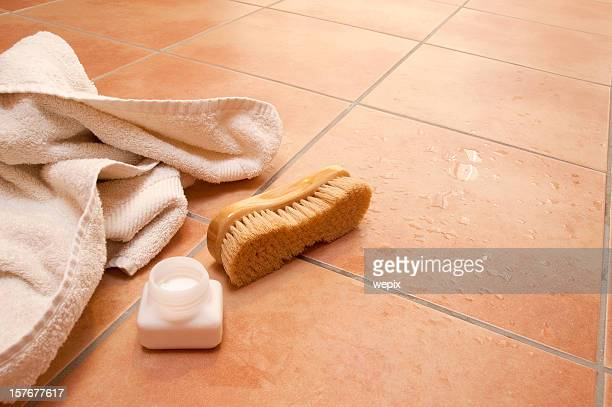 Wellness towel brush bath salts wet terracotta tile floor