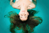 Wellness - young woman floating in Spa or swimming pool, she is very relaxed
