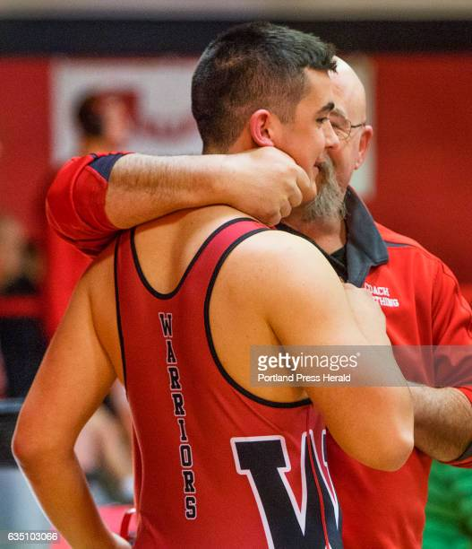 Wells Assistant Coach Jim Worthing hugs junior Nolan Potter after he was declared the winner by injury default in the 195 lb class during the Class B...
