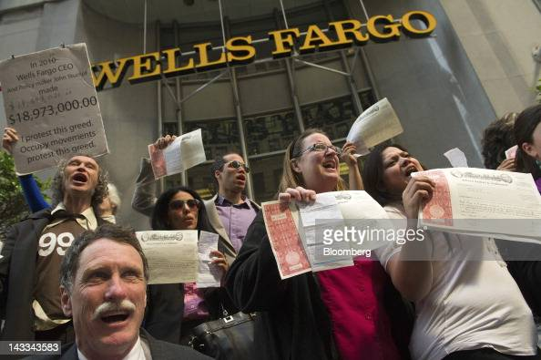 Wells Fargo Co shareholders hold up their share certificates and the citations they received for being arrested as they joined members of Occupy San...