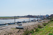 Looking back from the quayside to the town of Wells-next-the-Sea at low tide with small boats tied up along a jetty
