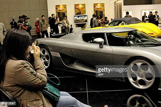 Welltodo Chinese customers gather to admire luxurious imported cars at an exhibition in Beijing on November 23 2008 China's economy is likely to grow...