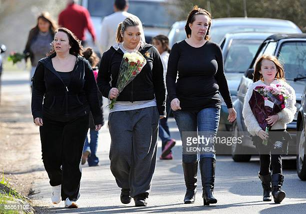 Wellwishers carry floral tributes to the home of reality television personality Jade Goody on March 22 2009 after the British reality television died...