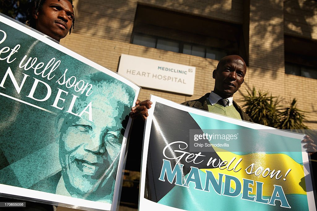 Well-wishers from South Africa and the Bahamas stand with signs outside the Mediclinic Heart Hospital where former South African President Nelson Mandela, 94, has spent the previous the week June 16, 2013 in Pretoria, South Africa. This is Nelson Mandela's fourth time in the hospital with a reoccuring lung infection since December of 2012.