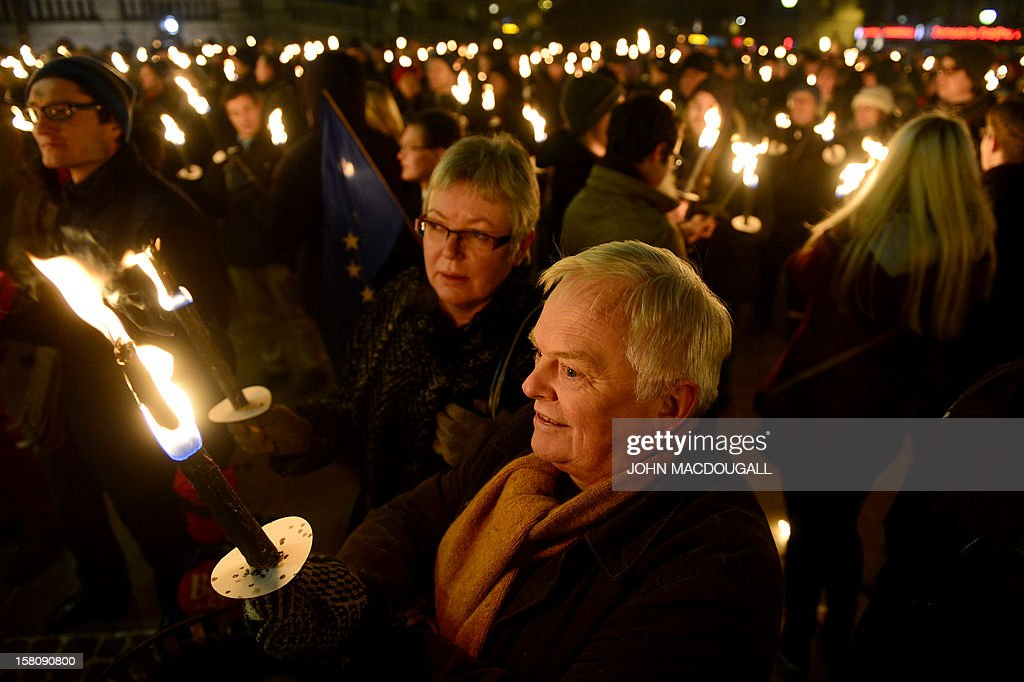 Wellwishers gather with torches and European flags under the balcony of the Grand Hotel to greet the Nobel peace prize winners before the Nobel Banquet taking place after the Nobel Peace Prize ceremony in Oslo on December 10, 2012. The EU collects this year's prestigious Nobel Peace Prize, with the bloc battered and divided by a three-year economic crisis threatening the continent's social stability.