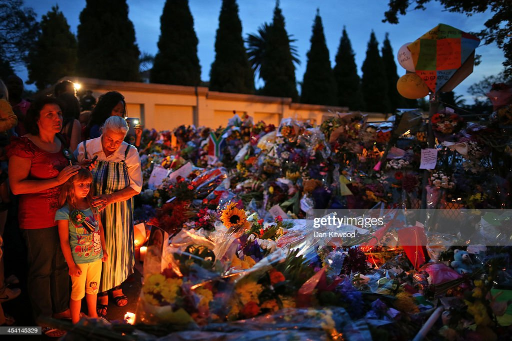 Wellwishers lay flowers outside the Houghton home of the former South African President Nelson Mandela on December 7, 2013 in Johannesburg, South Africa. Mandela, also known as Madiba, passed away on the evening of December 5th, 2013 at his home in Houghton at the age of 95. Mandela became South Africa's first black president in 1994 after spending 27 years in jail for his activism against apartheid in a racially-divided South Africa.