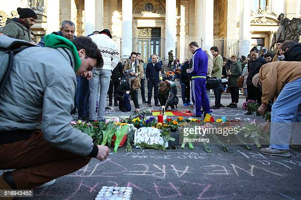 Wellwishers place flowers and floral tributes on Beursplein square as the Brussels stock exchange operated by Euronext NV stands beyond in Brussels...