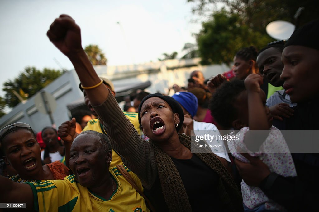 Wellwishers sing outside the Houghton home of the former South African President Nelson Mandela on December 7, 2013 in Johannesburg, South Africa. Mandela, also known as Madiba, passed away on the evening of December 5th, 2013 at his home in Houghton at the age of 95. Mandela became South Africa's first black president in 1994 after spending 27 years in jail for his activism against apartheid in a racially-divided South Africa.