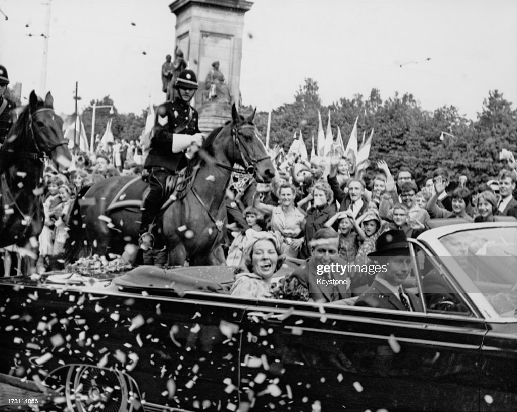 Wellwishers surround the car of Princess Beatrix of the Netherlands and her fiancee Claus van Amsberg after they announced the date of their wedding...