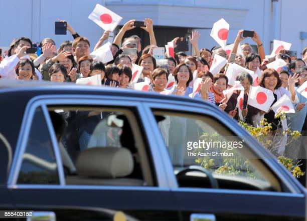 Wellwishers wave to a car carrying Emperor Akihito and Empress Michiko at Matsuyama Airport on September 29 2017 in Matsuyama Ehime Japan
