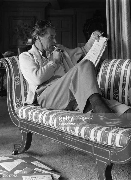 Welsh actor composer and songwriter Ivor Novello relaxes on his chaise longue while making a few last minute adjustments to the score of a song from...
