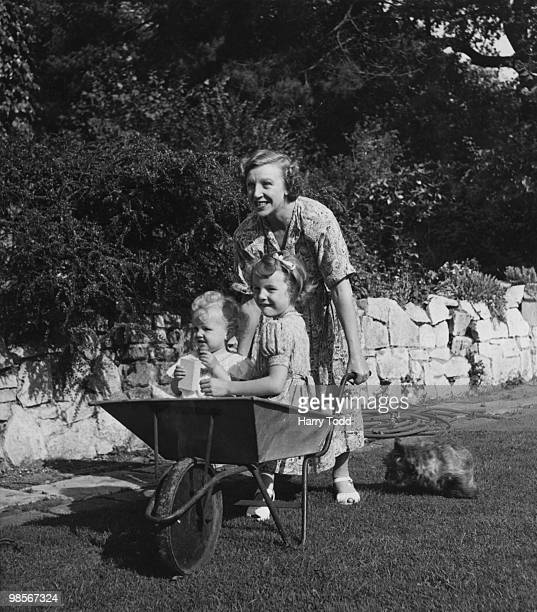 Welsh actress Doris Hare pushing her daughters Susan and Kathleen in a wheelbarrow in the garden at their home in Wimbledon London 4th October 1948