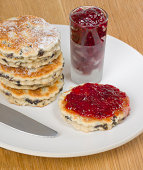 'Traditional Welsh Cakes or bakestones resting on a plate sprinkled with caster sugar, served with jam or jelly'