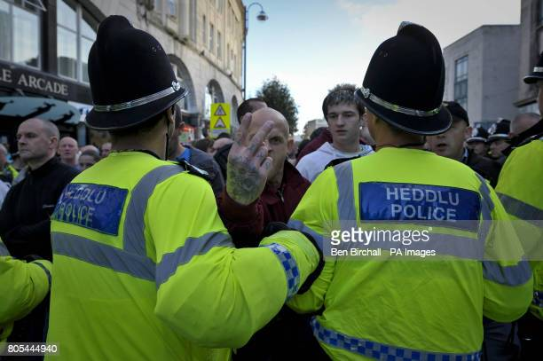 A Welsh Defence League protester shows two fingers to the camera showing the word 'skin' tattooed on his fingers as the their group is led away from...