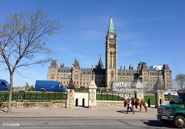 Welsh equestrian Megan Lewis walks her horse past Canada's parliament on May 7 2015 in Ottawa Ontario She is on the last leg of a sixyear around the...