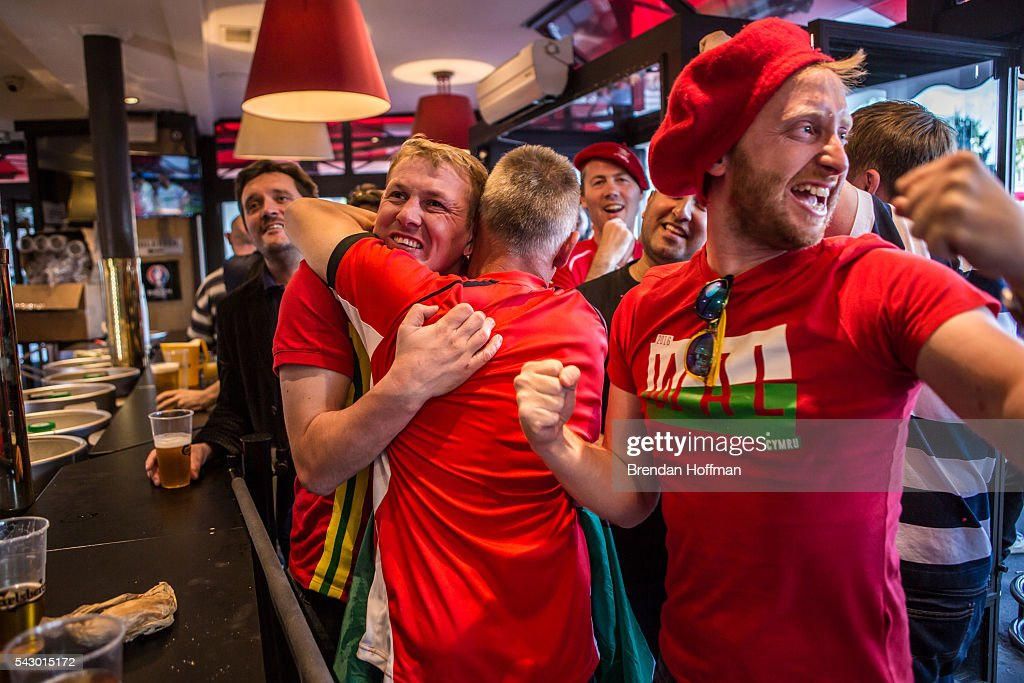 Welsh fans at a bar near the Parc des Princes stadium celebrate their team's victory during the football match between Wales and Northern Ireland during UEFA Euro 2016 tournament on June 25, 2016 in Paris, France. The two teams met in the Round of 16 at Parc des Princes in Paris, where Wales won 1-0.