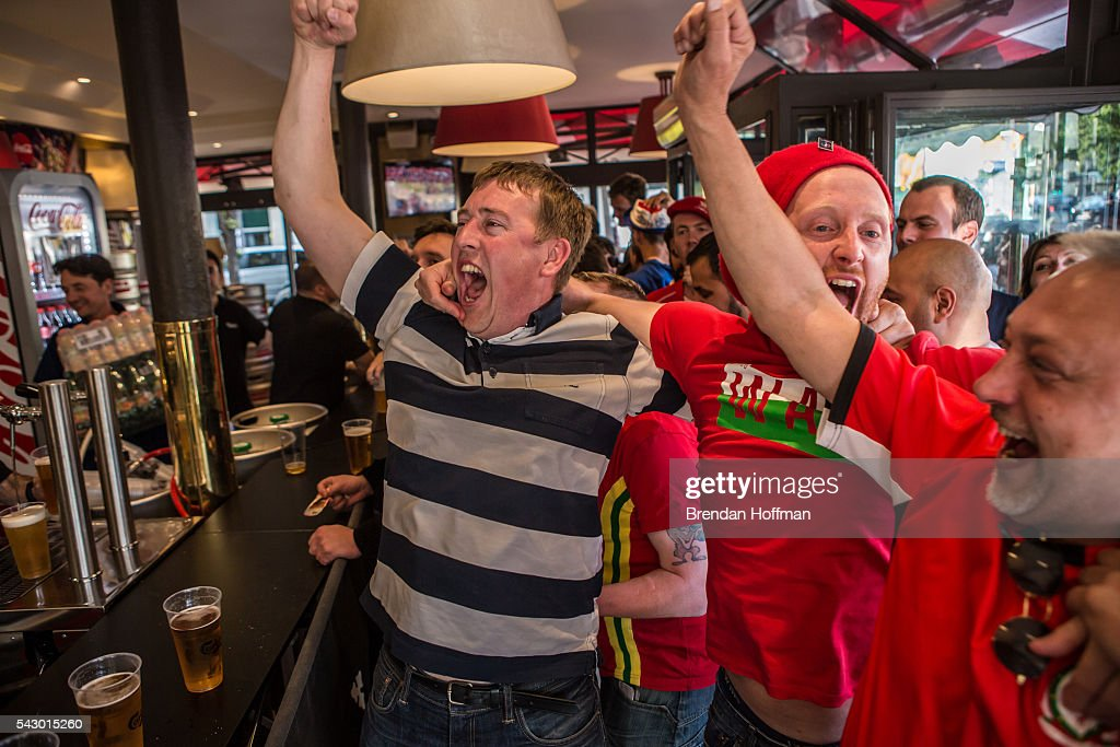 Welsh fans at a bar near the Parc des Princes stadium celebrate their team scoring a goal while watching a live television broadcast of the football match between Wales and Northern Ireland during UEFA Euro 2016 tournament on June 25, 2016 in Paris, France. The two teams met in the Round of 16 at Parc des Princes in Paris, where Wales won 1-0.