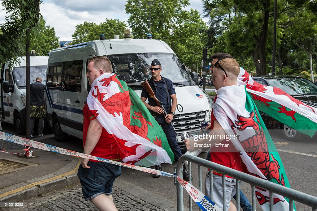Welsh fans walk past a police officer near the Parc des Princes stadium ahead of the football match between Wales and Northern Ireland during UEFA Euro 2016 tournament on June 25, 2016 in Paris, France. The two teams met in the Round of 16 at Parc des Princes in Paris, where Wales won 1-0.