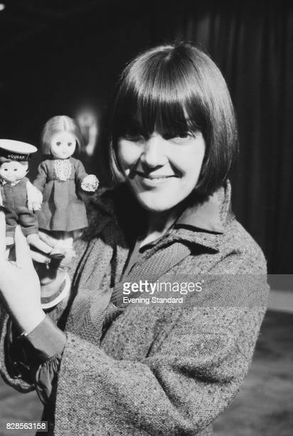 Welsh fashion designer Mary Quant holds two dolls 29th january 1975