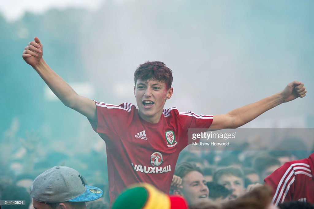 Welsh football fans react to a goal by Wales while watching the Wales v Belgium Euro 2016 quarter-final match on a big screen at the Cardiff fan zone in Coopers Field on July 1, 2016 in Cardiff, Wales.
