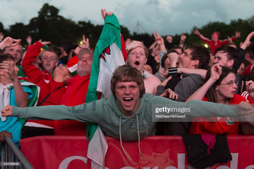 Welsh football fans react to a third goal by Wales while watching the Wales v Belgium Euro 2016 quarter-final match on a big screen at the Cardiff fan zone in Coopers Field on July 1, 2016 in Cardiff, Wales.