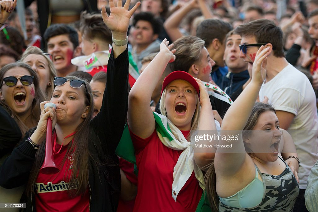 Welsh football fans react to Wales' second goal, scored by Hal Robson-Kanu of Wales while watching the Wales v Belgium Euro 2016 quarter-final match on a big screen at the Cardiff fan zone in Coopers Field on July 1, 2016 in Cardiff, Wales.