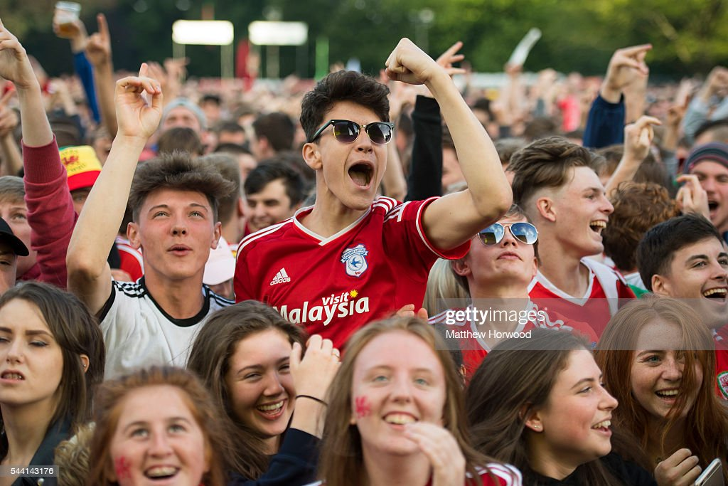 Welsh football fans watch the Wales v Belgium Euro 2016 quarter-final match on a big screen at the Cardiff fan zone in Coopers Field on July 1, 2016 in Cardiff, Wales.
