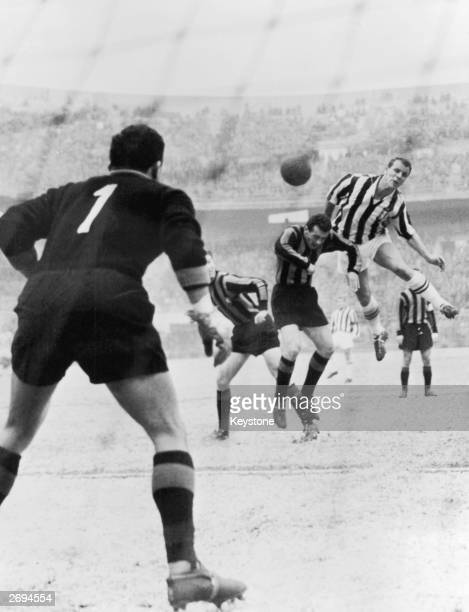 Welsh footballer John Charles leaping above two Inter Milan players to score for Juventus