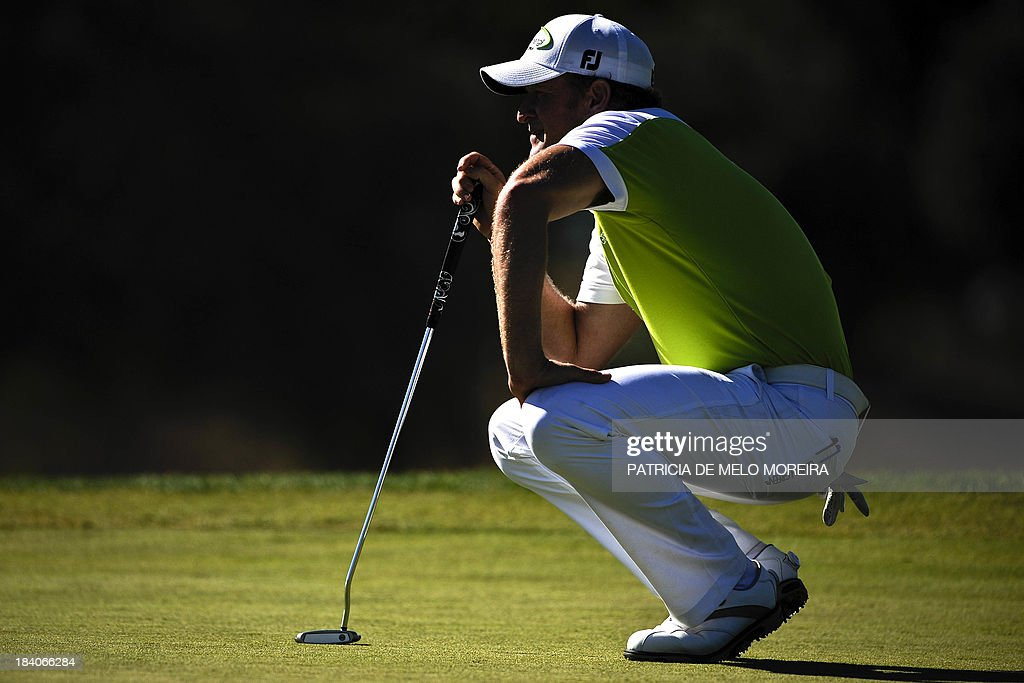 Welsh golfer Jamie Donaldson lines up his putt on the 9th during the second day of the Portugal Masters golf tournament at Victoria Golf Course in Vilamoura, southern Portugal on October 11, 2013.