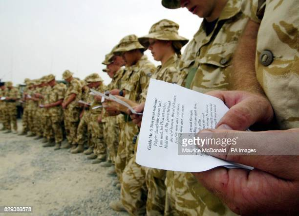 A Welsh guard holds an order of service as Padre Captain Mark GrantJones reads the service to B Company of the First Queen Dragoon Guards as they get...