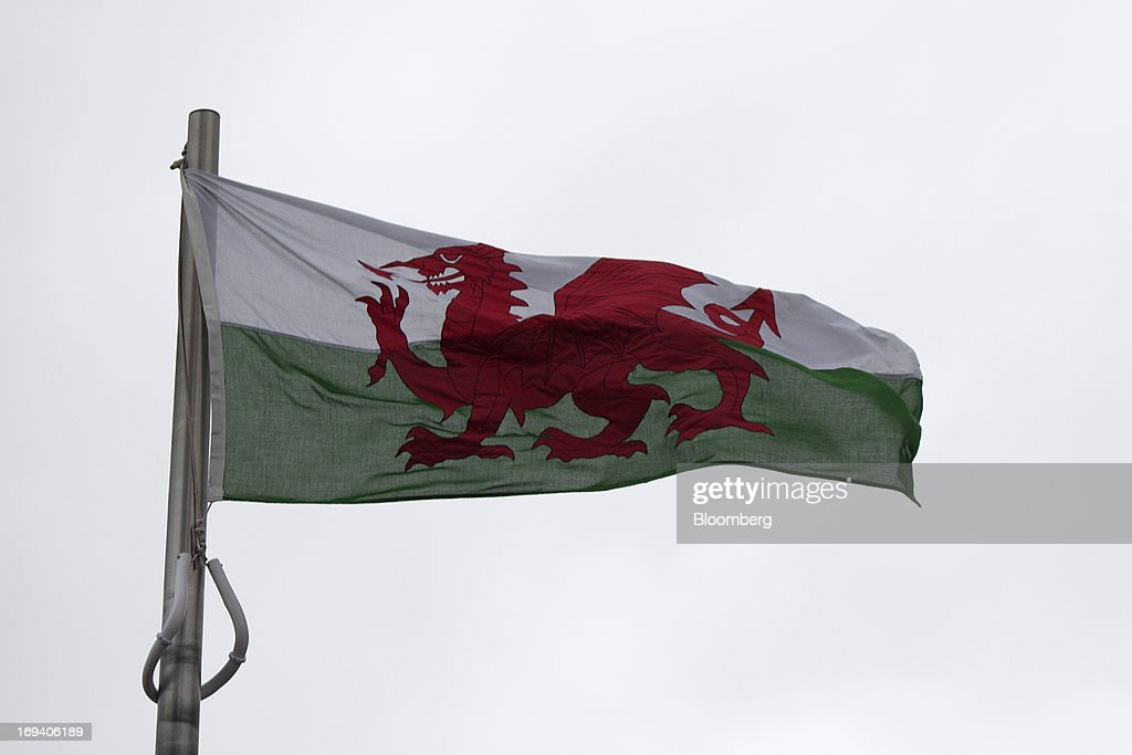 A Welsh national flag flies from a flagpole near the Senedd, or National Assembly for Wales government building in Cardiff, U.K. on Thursday, May 23, 2013. Bank of England Markets Director Paul Fisher said policy makers must continue to provide support to the British economy so that companies and consumers have room to reduce debts and rebuild confidence. Photographer: Simon Dawson/Bloomberg via Getty Images