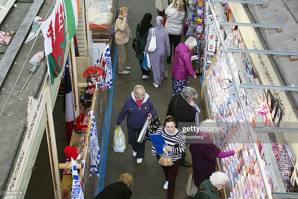 A Welsh national flag hangs above a sports goods stall as shoppers browse items for sale at an indoor market in Cardiff, U.K. on Thursday, May 23, 2013. Bank of England Markets Director Paul Fisher said policy makers must continue to provide support to the British economy so that companies and consumers have room to reduce debts and rebuild confidence. Photographer: Simon Dawson/Bloomberg via Getty Images