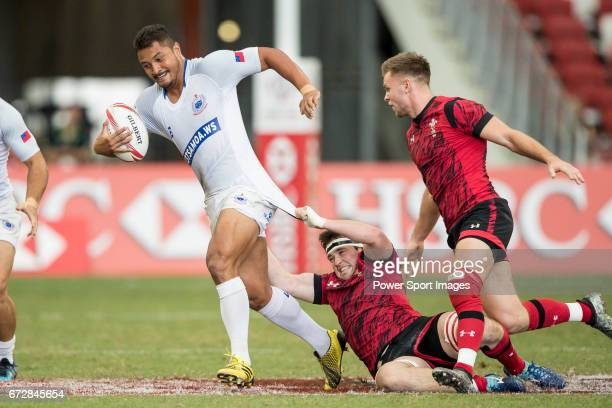 Welsh player tries to tackle Alamanda Motuga of Samoa during the match Wales vs Samoa Day 2 of the HSBC Singapore Rugby Sevens as part of the World...