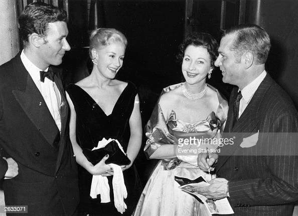 Welsh playwright John Osborne with his wife actress Mary Ure chatting with actor Sir Laurence Olivier and his wife actress Vivien Leigh after a...