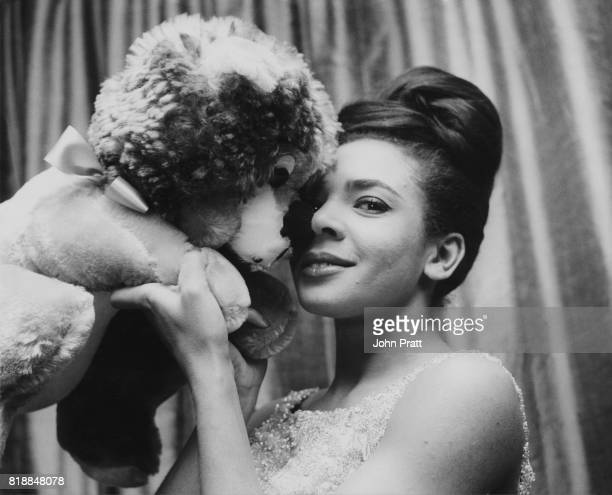 Welsh singer Shirley Bassey hugs a toy dog mascot before a show December 1962