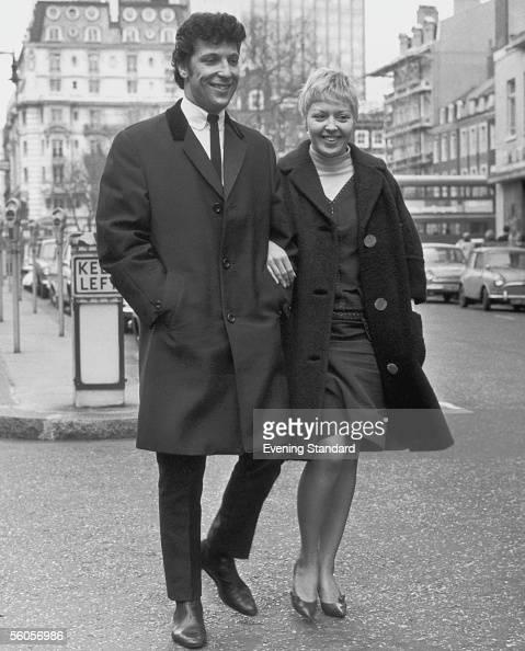 Welsh singer Tom Jones and his wife Linda walking down a street 1965