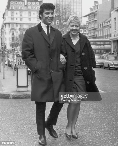 Welsh singer Tom Jones and his wife Linda walking down a street 1965