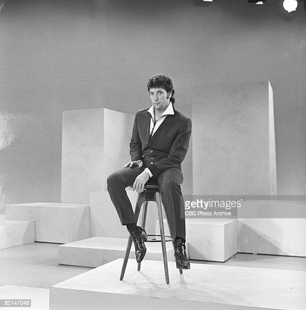 Welsh singer Tom Jones sits on a stool on stage during rehearsal for an appearance on 'The Ed Sullivan Show' New York New York June 13 1965